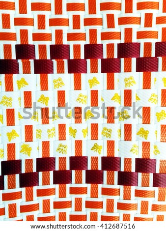 Decorative patterns woven baskets of beautiful red gold and orange plastic - stock photo