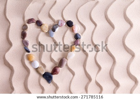 Decorative pebble heart of waterworn alluvial quartzite, agate and basalt stones symbolic of love and romance on golden beach sand with an ornamental pattern of wavy lines and copy space - stock photo