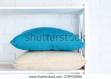 Decorative pillows on shelf on wall background - stock photo