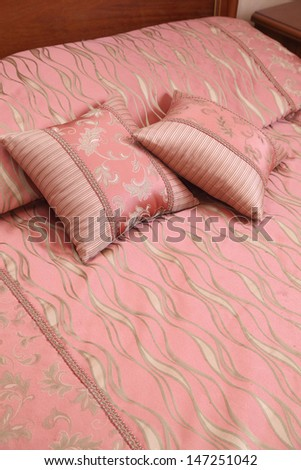 decorative pillows with an ornament on a bed about a bed back - stock photo