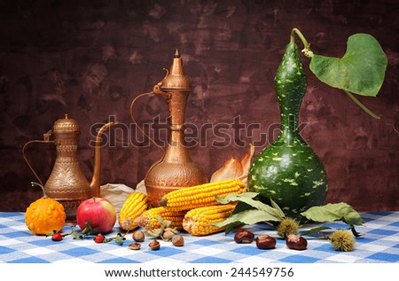 Decorative pumpkins, corn and metal jugs on the table - stock photo