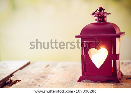 Decorative red metal lantern with a heart cutout lit by a glowing candle with copyspace for Valentines or Christmas - stock photo