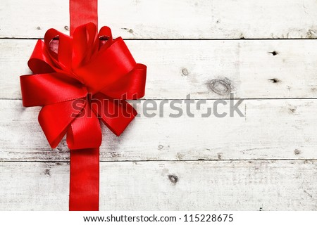 Decorative red ribbon and bow on a background of white painted rustic boards with copyspace