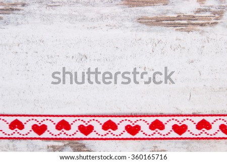Decorative ribbon with red heart shape on old rustic wooden background, decoration for valentines day, copy space for text - stock photo