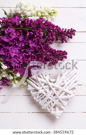 Decorative rustic heart and  fresh white and violet lilac flowers on white painted wooden planks. Selective focus. Close up. - stock photo