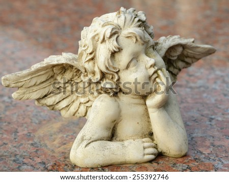 decorative sculpture of putto isolated on granite surface - stock photo