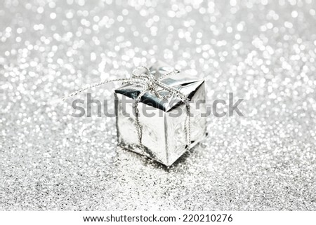 Decorative silver box with holiday gift on shiny glitter background - stock photo