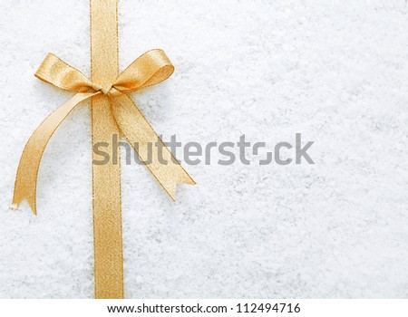 Decorative simple gold ribbon and bow on a background of winter snow with copyspace for your Christmas or festive greeting - stock photo