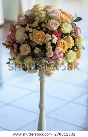 Decorative wedding posy of fresh beautiful flowers of roses and peony white pink violet purple yellow lilac and orange colours in slim long vase on tile floor background, vertical picture - stock photo