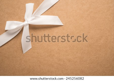 Decorative white ribbon and bow over cardboard