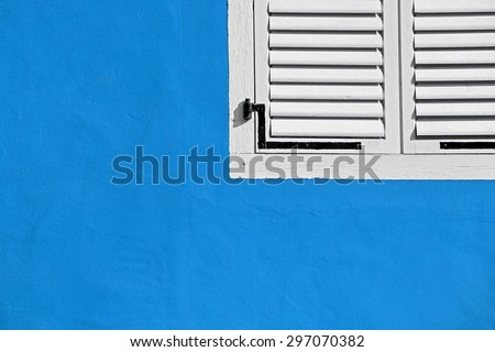 Decorative white window on an old blue stucco wall. - stock photo