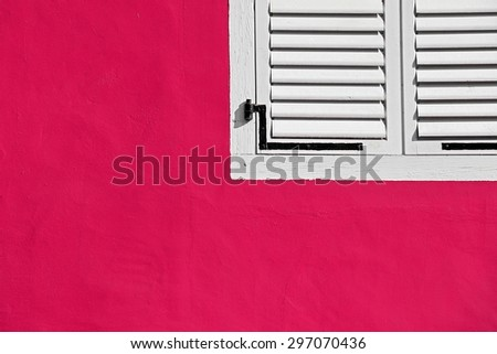 Decorative white window on an old pink stucco wall. - stock photo