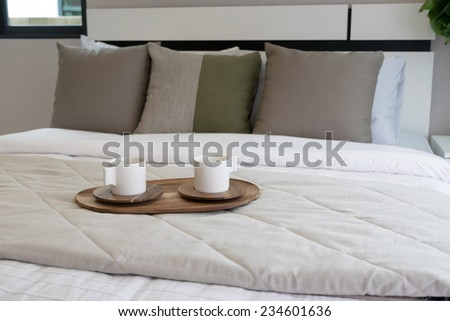 Decorative wooden tray with tea set on bed