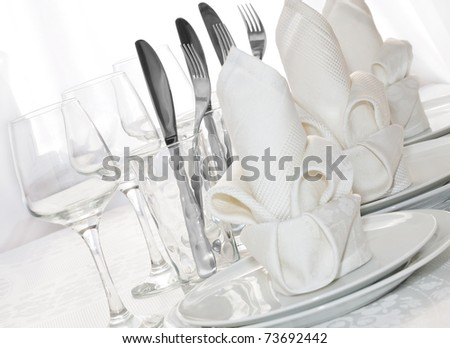 Decoratively folded napkins with glasses, glasses and cutlery - stock photo