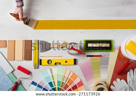 Decorator holding a paint brush and painting a wooden surface, work tools and swatches at bottom, banner with copy space - stock photo