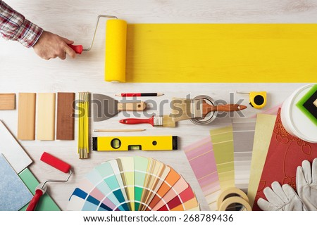 Decorator holding a painting roller and painting a wooden surface, work tools and swatches at bottom, banner with copy space - stock photo