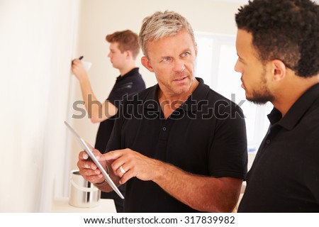 Decorator instructing colleague painting a room - stock photo