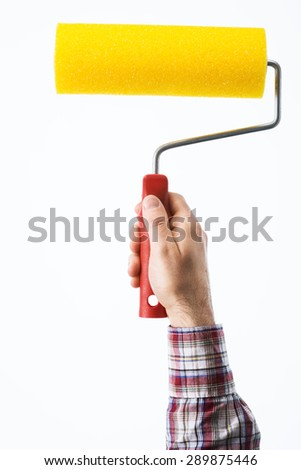Decorator's male hand holding a painting roller on white background, hobby and home renovation concept - stock photo