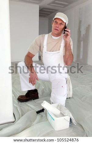 Decorator speaking to dissatisfied customer over the phone - stock photo