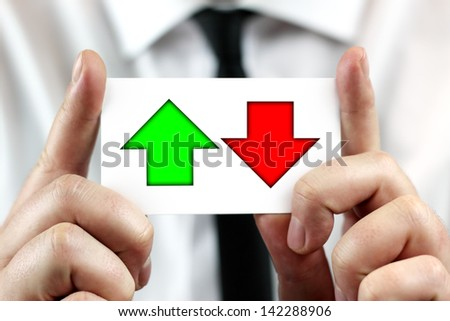 Decreases and increases in stock market, exchange rates, up and down. Businessman in white shirt with a black tie, shows business card. - stock photo