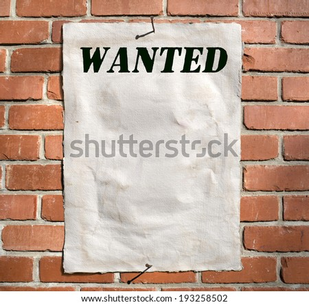 Decree (notice) on wanted criminals on a brick wall - stock photo