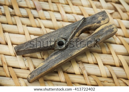 Decrepit wooden clothespin lying on straw mat - stock photo