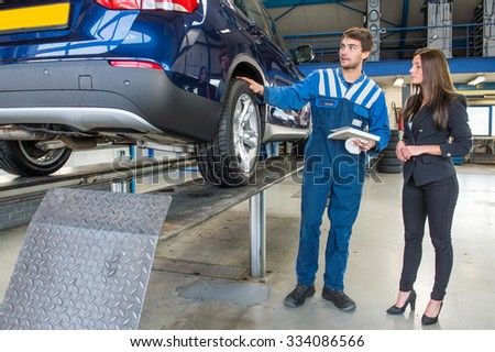 Dedicated and professional service mechanic, showing a customer around her car, which has just been serviced and equipped with winter tires. The mechanic is holding a cloth - stock photo