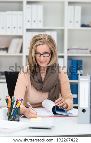 Dedicated businesswoman with a friendly smile sitting working hard on paperwork at her desk peering over the top of her glasses at the camera - stock photo