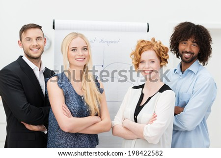 Dedicated confident young multiracial business team posing with folded arms in front of a flip chart looking at the camera with warm friendly smiles