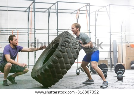 Dedicated man shouting by climbing wall in gym - stock photo