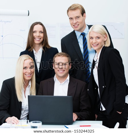 Dedicated professional diverse young business team posing grouped at a desk with a laptop smiling at the camera