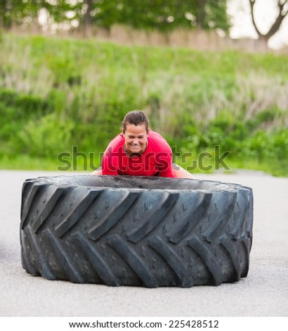 Dedicated woman lifting large tractor tire outdoors - stock photo