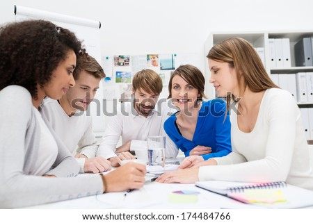 Dedicated young business team in a meeting sitting grouped around a table in the office holding a serious discussion with focus to an attractive businesswoman at the back - stock photo