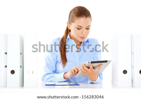 Dedicated young businesswoman hard at work at her desk on a tablet computer surrounded by large office binders - stock photo