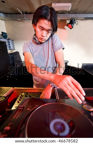 Dee Jay behind the turntables in a nightclub - stock photo