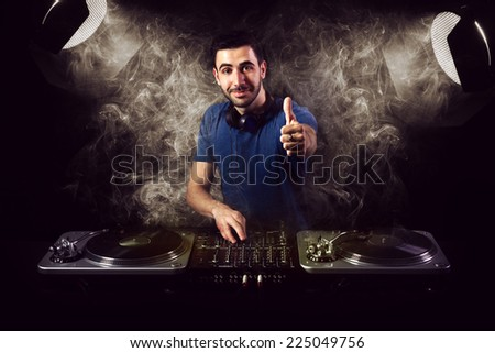Deejay smiling to camera while showing ok sign. He is illuminated by two vintage spot light reflectors. - stock photo