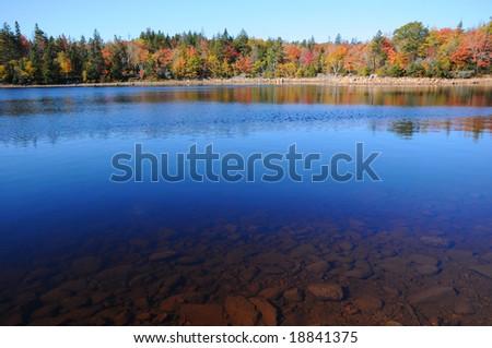 Deep blue lake and Autumn foliage - stock photo