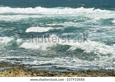 Deep blue ocean waves white with foam roll on rocky shore. - stock photo