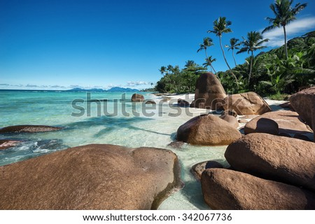 Deep blue sky and beautiful beach with huge stones / outdoors photo of picturesque Seychelle islands - stock photo