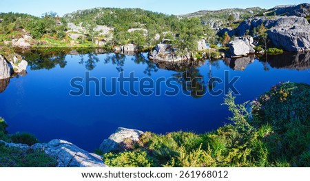 Deep blue small mountain Norway lake with rocky shore - stock photo