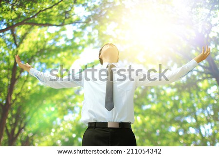 Deep breathing carefree business man with tree in the forest, asian - stock photo