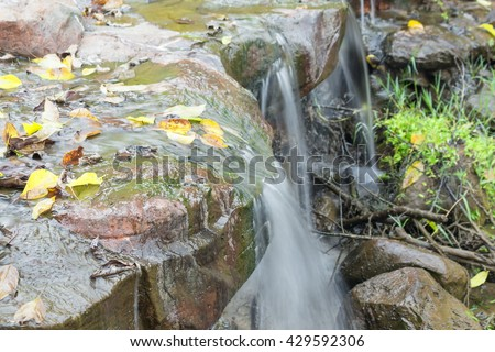 Deep forest Waterfall small, Beautiful  of waterfalls with soft flowing water and large colored rocks.( Blur blurred Waterfall) - stock photo