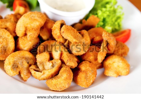 Deep-fried champignon mushrooms with lettuce, tomatoes and mayonnaise - stock photo