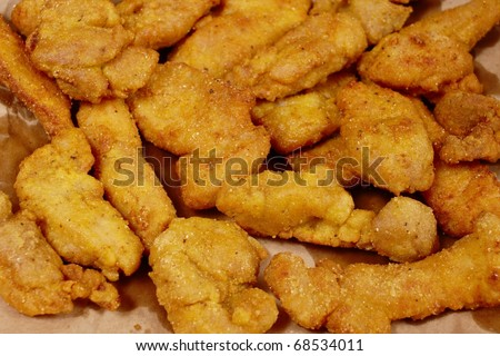Deep-fried chicken nuggets draining on paper towel - stock photo