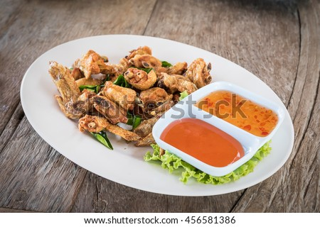 Deep fried chicken wings with salt and herbs in dish on wooden background,Top view - stock photo