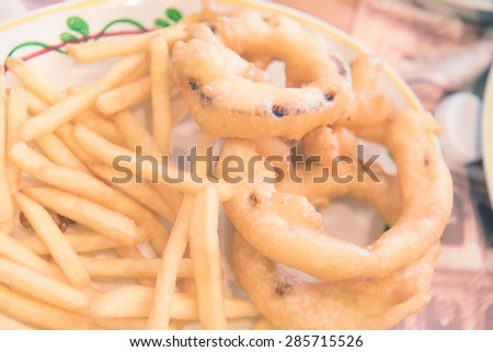 Deep fried crispy onion rings with tomato sauce and french fries - Vintage picture style, Shallow DOF - stock photo