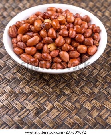 Deep fried peanuts in white bowl over rustic wicker background