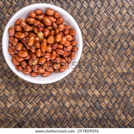 Deep fried peanuts in white bowl over rustic wicker background - stock photo