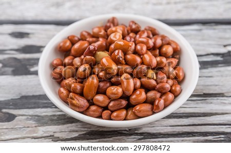 Deep fried peanuts in white bowl over rustic wooden background