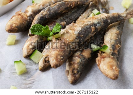 deep fried sardines with lemon and salad on white paper - stock photo
